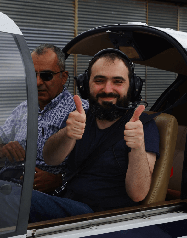 Lionel giving a thumbs up while seated in a plane