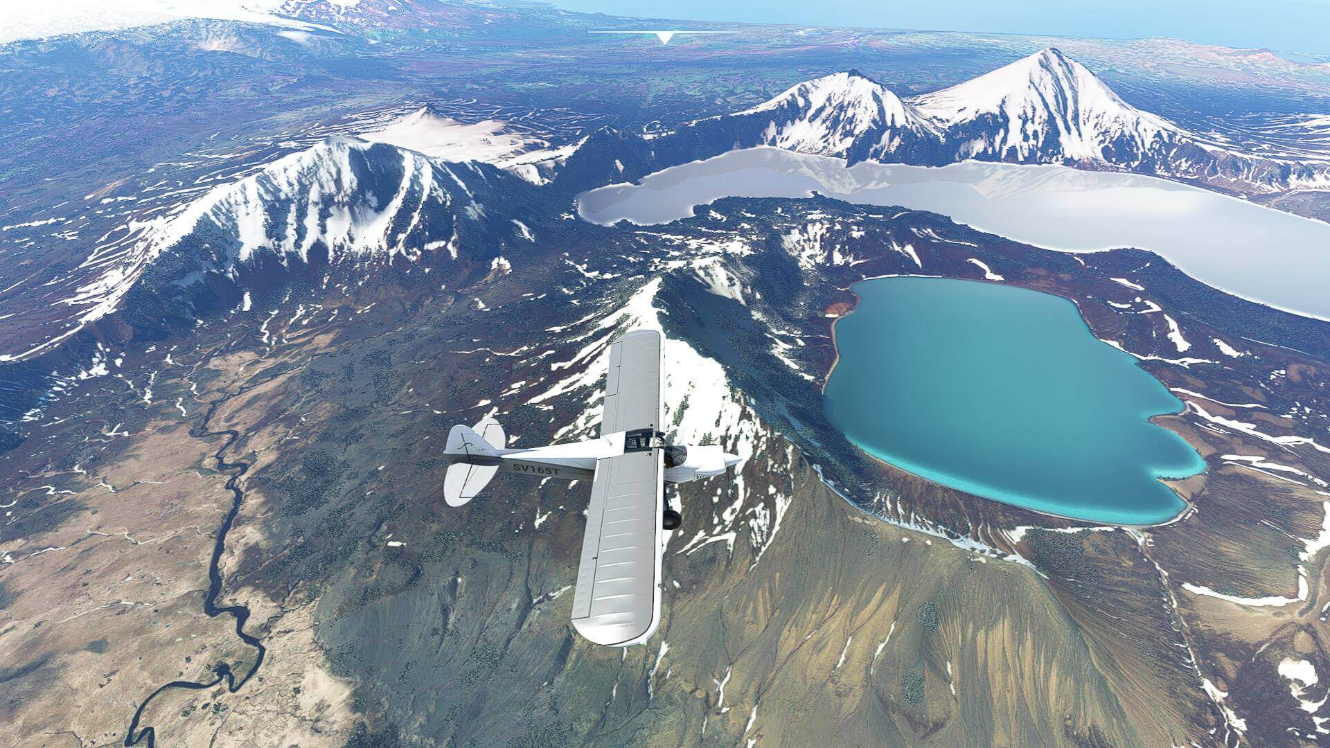 Plane flying over a blue lake in the snowy mountains