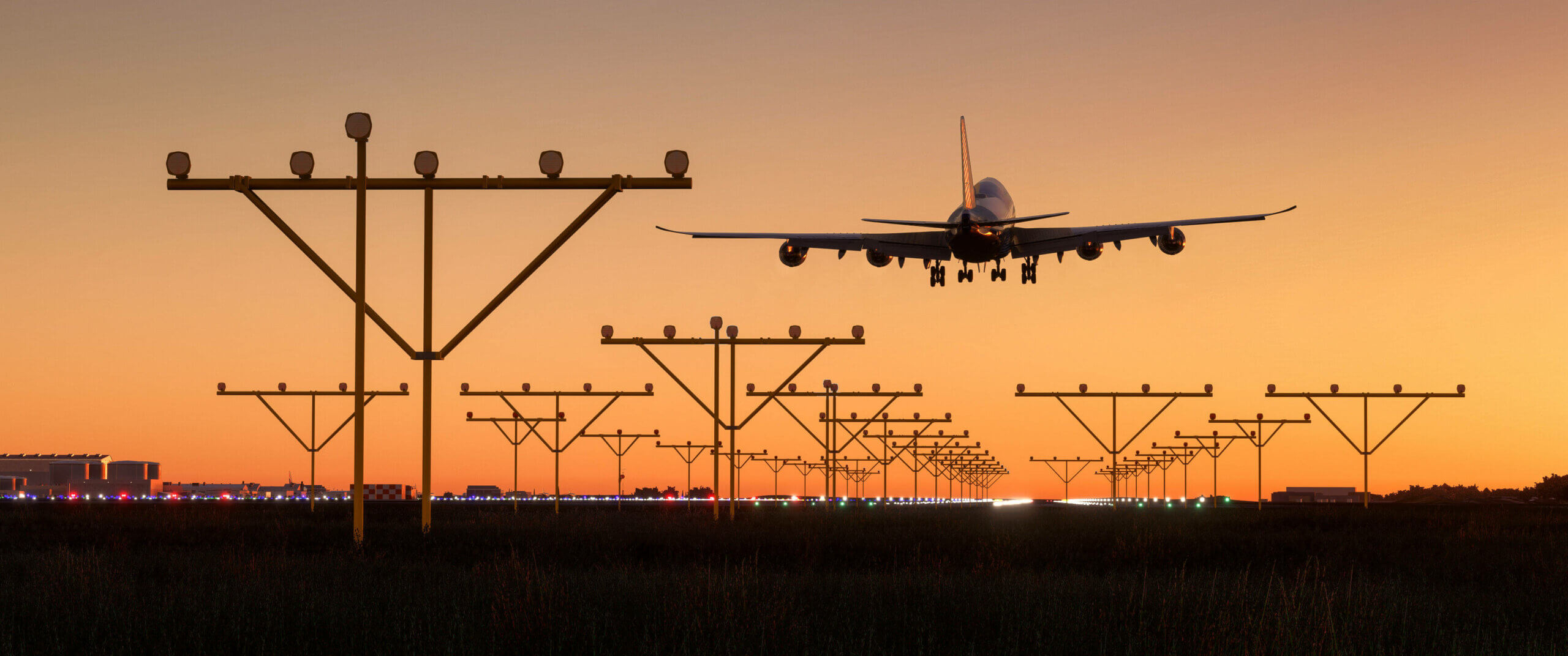 Plane coming in for final approach during sunset