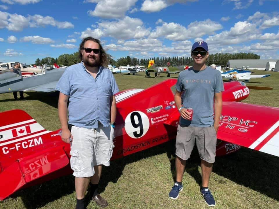 Two men are standing in front of a red racing plane